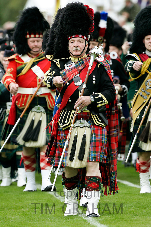 Drum Major leads massed band of Scottish pipers at Braemar Games Highland Gathering