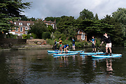 A group of young people paddle past a riverside period house, lead by a paddle-board instructor  at Thorpe St Andrew, on 2nd July 2021, in Norwich, England.