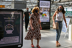 © Licensed to London News Pictures. 16/07/2021. Edinburgh, Scotland, UK. Commuters wearing face coverings walk past 'Wear a face covering' poster at Edinburgh Waverley station. From Monday 19 July, wearing face coverings on public transport in England will no longer be a legal requirement. However, passengers travelling in Scotland and Wales will be required to wear face coverings on public transport beyond July 19. Photo credit: Dinendra Haria/LNP