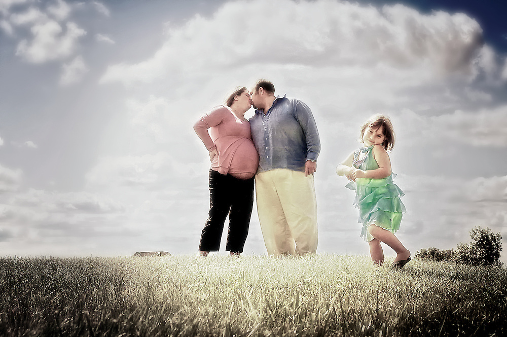 Pregnant couple kiss while daughter dances in open field.