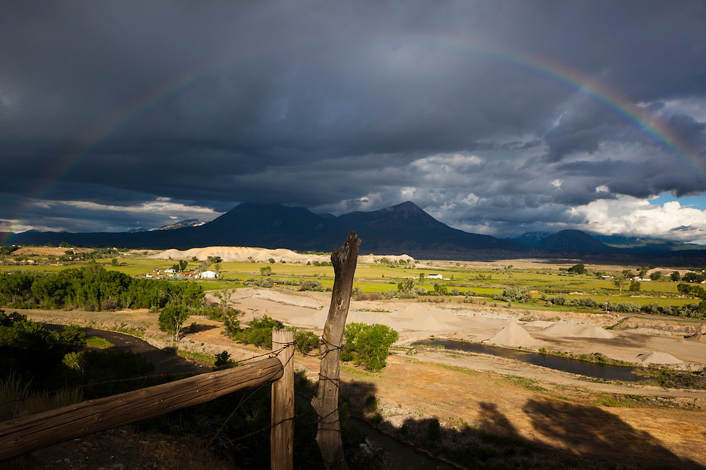 A rainbow and storm clouds over the North Fork Valley near Hotchkiss, Colorado. Mount Lamborn and Landsend Peak (l-r) rise prominently across the valley.