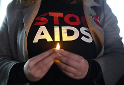 People attending a candlelit vigil for World Aids Day, in Spring Gardens, London.