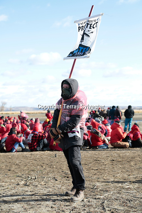 An opponent of the Dakota Access oil pipeline carries a sign during a demonstration on November 18, 2016. Cannon Ball, North Dakota, United States.