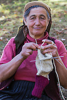 Woman (62 years old) knitting socks from own sheep wool in the garden of her nearby farmhouse in the village of Isverna. Mehedinti Plateau Geopark, Geoparcul Platoul Mehedinți, Isverna, Romania.