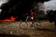 A boy rides by a massive oil fire in Malakal the capital of Upper Nile State which holds much of South Sudan's vast oil wealth and many different militias on April 30, 2010.