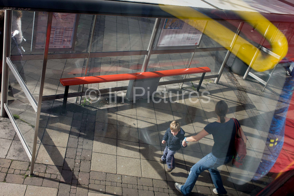 Mother and active child with aerial view of bus stop shadows and reflections. As we look down on the urban scene, the mum grabs the child by the hand to stop him running off in a strange city. They have just alighted from the double-decker bus that has dropped them off at Waterloo on the southbank of the Thames in central London. Sunlight has created a pattern of shadows from the glass shelter screen and reflections from the top deck seating is seen in the foreground.