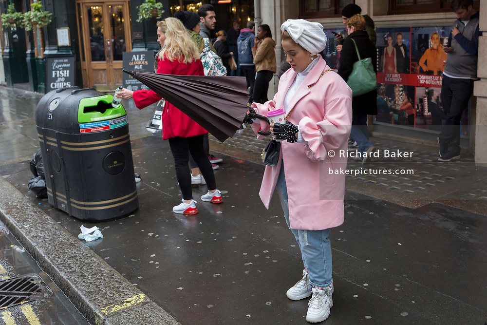 A stylish lady in pink adjusts her umbrella in St. Martin's Lane, Westminster, on 9th April 2019, in London, England.