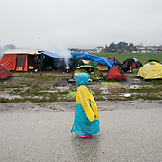 A lonely refugee child standing under the rain in the middle of the road that leads to the transit camp of Idomeni, Greece. <br /> <br /> Thousands of refugees are stranded in Idomeni unable to cross the border. The facilities here are stretched to the limit and the conditions are appalling. It's raining, it's cold there is mud everywhere and there is no hope that the border will open anytime soon.