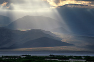 Sunlight and crepuscular rays through storm clouds on an alluvial fan below the Panamint Mountains, Death Valley National Park, California - * USPS STAMP IMAGE *