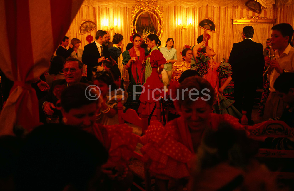 A lively group of friends, family and corporate clients have gathered to enjoy a traditional evening of Flamenco, Tapas and sociable gossip while at the Feria, an annual festival of culture and dance in Seville, Andalucia, Spain. In the centre are two ladies talking and two younger girls practicing their dance moves amid frivolous partying. Everyone here is impeccably dressed in smart jackets and tasteful ties and traditional Spanish dresses. It is a lively event that Seville holds annually in the vast fairground area on the far bank of the Guadalquivir River. Rows of temporary marquee tents, or casetas, host families, corporations and friends into the late hours during the April Fair which begins begins two weeks after the Semana Santa, or Easter Holy Week in the Andalusian capital.
