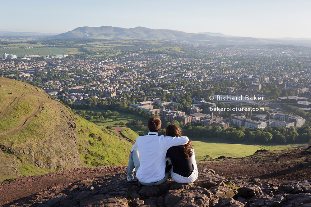 "A young couple gaze out towards the city of Edinburgh from the summit of Arthur's Seat in Holyrood Park, on 26th June 2019, in Edinburgh, Scotland. Arthur's Seat is an extinct volcano which is considered the main peak of the group of hills in Edinburgh, Scotland, which form most of Holyrood Park, described by Robert Louis Stevenson as ""a hill for magnitude, a mountain in virtue of its bold design"". The hill rises above the city to a height of 250.5 m (822 ft), providing excellent panoramic views of the city and beyond."
