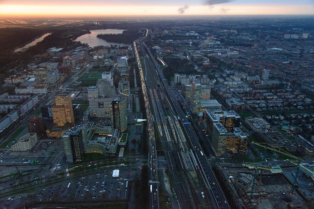 Nederland, Noord-Holland, Amsterdam, 16-01-2014; zicht op de Zuidas en de Ring A10 in de avondschemering en bij ondergaande zon. Schiphol aan de horizon. Omgeving Station Zuid-WTC, World Trade Centre (WTC) en hoofdkantoor ABN-AMRO.<br /> Verder in beeld , de woontorens Symphony 1 en 2 (onderdeel Gershwin), de Vinoly-toren en Ito-toren (onderdeel Mahler4), Atrium.<br /> Zuid-as, 'South axis', financial center in the South of Amsterdam, with o.a. headquarters of former ABN AMRO, World Trade Centre (WTC) en Ring Road A10. Amsterdam equivalent of 'the City', financial district. <br /> luchtfoto (toeslag op standaard tarieven);<br /> aerial photo (additional fee required);<br /> copyright foto/photo Siebe Swart.<br /> aerial photo (additional fee required);<br /> copyright foto/photo Siebe Swart.