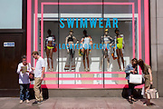 Shoppers in front of a window display featuring swimwear in Topshop's Oxford Street store in central London.