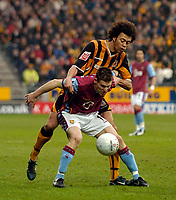 Photo: Jed Wee.<br />Hull v Aston Villa. The FA Cup. 07/01/2006.<br />Aston Villa's James Milner uses his body to shield the ball from Hull's Jason Price.