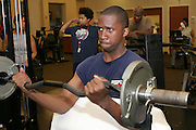 (MODEL RELEASED IMAGE).Every week, the Revis family (foreground, Brandon curling weights; background, left to right, Rosemary, Tyrone, and Ron) faithfully trekked to the health club in the Wakefield Medical Center, a hospital complex in Raleigh, North Carolina, for two-hour exercise sessions. They enjoyed the workouts, but found them so time-consuming that they wound up eating more fast food than ever. Fearing its potential impact on their health, they ultimately gave up the club in favor of dining and exercising at home. Hungry Planet: What the World Eats (p. 268).