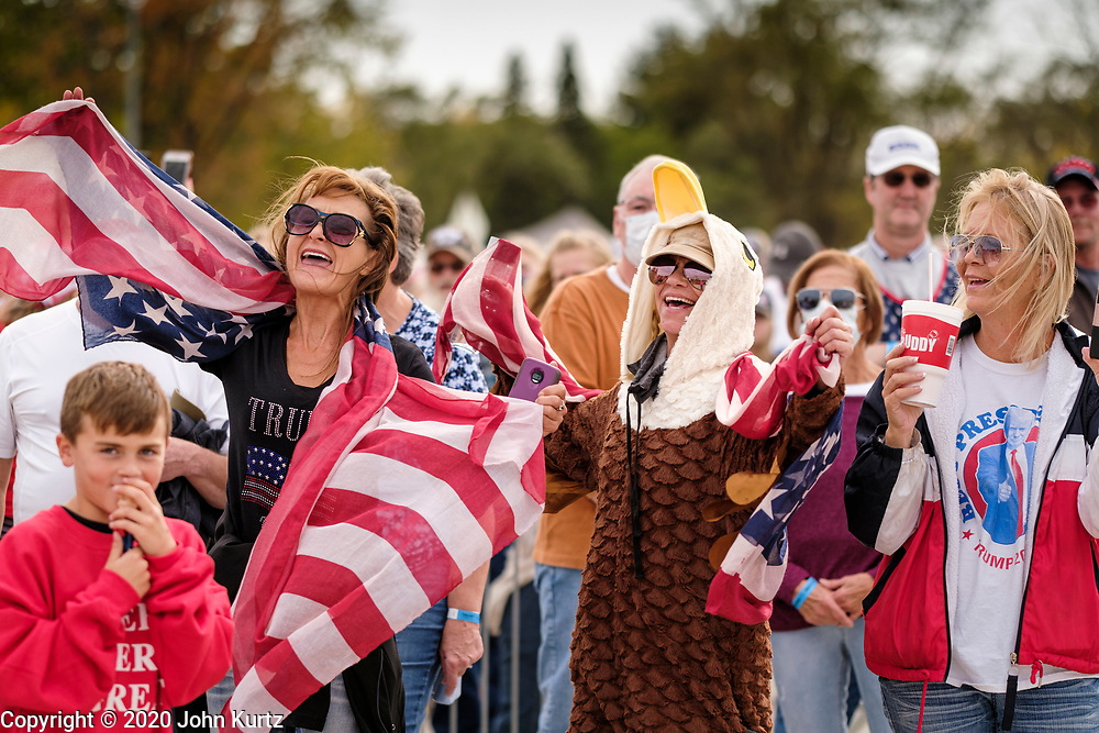 """14 OCTOBER 2020 - DES MOINES, IOWA: Women listen to people sing the Lee Greenwood song """"God Bless the USA"""" before a Donald Trump reelection rally. About10,000 people were expected at the Des Moines International Airport for a campaign rally supporting the reelection of President Donald Trump. Trump spoke at the rally, despite testing positive for COVID-19 less than three weeks ago. The rally did not meet the CDC guidelines for a safe gathering in the time of Coronavirus and violated Iowa's health emergency declarations barring gatherings of more than 25 people. This week Iowa exceeded 101,000 cases of COVID-19 and a surge in hospitalizations for COVID-19.       PHOTO BY JACK KURTZ"""