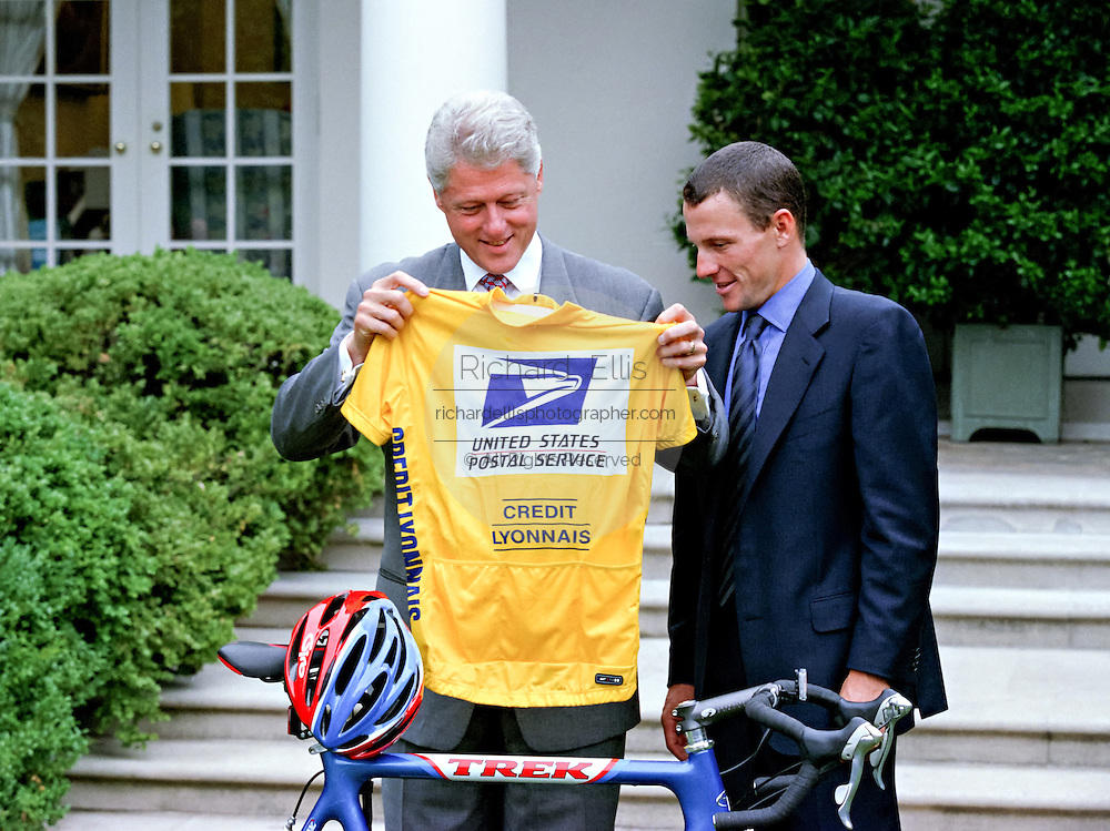 U.S President Bill Clinton holds a cycling team shirt given him by Lance Armstrong, 1999 winner of the Tour de France, in the Rose Garden of the White House August 10, 1999. Armstrong also gave the president a replica of the bike Armstrong used in the race.