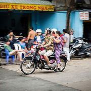 Motor scooter driving through busy street market in Saigon