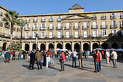 Men stand around in the square in Casco Viejo (old town) in Bilbao on a sunny October Sunday morning. Some exchange football cards.