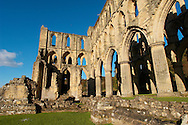 Rievaulx Abbey main church, side view. North Yorkshire, England . Rievaulx Abbey was a Cistercian abbey in Rievaulx, situated near Helmsley in the North York Moors National Park, North Yorkshire, England. Rievaulx Abbey was one of the great abbeys in England until it was seized under Henry VIII of England in 1538 during the dissolution of the monasteries. Founded in 1132 by twelve monks from Clairvaux Abbey. Rievaulx Abbey remote location was well suited to the order's ideal of a strict life of prayer and self-sufficiency with little contact with the outside world. <br /> <br /> Visit our MEDIEVAL PHOTO COLLECTIONS for more   photos  to download or buy as prints https://funkystock.photoshelter.com/gallery-collection/Medieval-Middle-Ages-Historic-Places-Arcaeological-Sites-Pictures-Images-of/C0000B5ZA54_WD0s