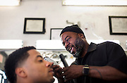 MILWAUKEE, WI - NOVEMBER 17: Cedric Fleming, right, laughs as he cuts the hair of a customer at Upper Cutz barbershop on Thursday, November 17, 2016.