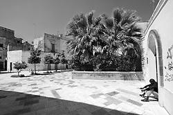 Lecce - Un extracomunitario si riposa nella piazzetta in Via delle Giravolte.