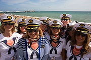 A group of young Scottish women gather for a portrait on Brighton seafront during their Hen weekend. One of their number is soon to be married and they are holidaying in this southern English seaside resort wearing matching nautical sailor caps and sunglasses, enjoying the warm coastal weather on May Bank Holiday. Behind them is the calm sea and the Victorian Palace Pier. Seagulls wheel overhead during this busy long weekend and the girls are revelling in their fun away from partners or husbands, escaping the tedium of the working week.