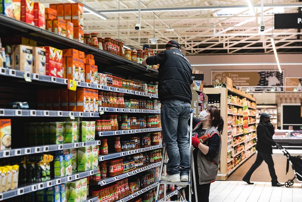 """Deux employés équipés de masques de protection  remettent en rayon des produits alimentaires dans le rayon des sauces salées, lors de l'arrivée des premiers clients dans le supermarché """"INTERMARCHÉ"""", La Loupe, région Centre, France, le 19 mars 2020.<br /> Two employees equipped with protective masks put food products on the shelf in the salted sauces department, when the first customers arrive in the supermarket """"INTERMARCHÉ"""", La Loupe, Center region, France, March 19, 2020."""