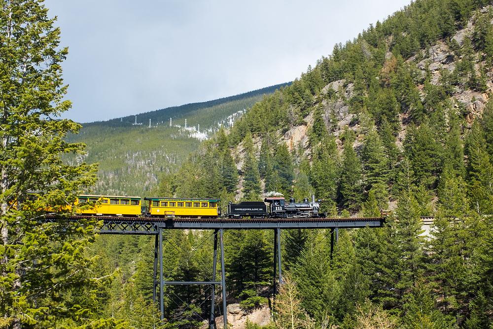 A steam powered locomotive on the Georgetown Loop Railroad crosses the Devil's Gate High Bridge above Clear Creek in Georgetown Colorado.