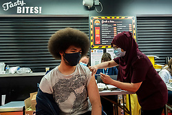 """© Licensed to London News Pictures. 27/06/2021. WATFORD, UK. Ben Adonis (aged 19) receives a first dose of the Pfizer vaccine at a pop-up mass vaccination clinic at Watford FC's Vicarage Road Stadium as part of the """"Grab a jab"""" campaign. The NHS is also promoting a number of walk-in clinics this weekend across the capital to try to increase the number of over 18s receiving a jab as cases of the Delta variant are reported to be on the rise..  Photo credit: Stephen Chung/LNP"""