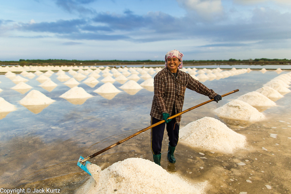 24 APRIL 2013 - SAMUT SONGKHRAM, SAMUT SONGKHRAM, THAILAND: Workers in a salt field in Samut Songkhram, Thailand, rake salt into piles during the salt harvest in Samut Songkhram, Thailand. The 2013 salt harvest in Thailand and Cambodia has been impacted by unseasonably heavy rains. Normally, the salt fields are prepped for in December, January and February, when they're leveled and flooded with sea water. Salt is harvested from the fields from late February through May, as the water evaporates leaving salt behind. This year rains in December and January limited access to the fields and rain again in March and April has reduced the amount of salt available in the fields. Thai salt farmers are finishing the harvest as best they can, but the harvest in neighboring Cambodia ended 6 weeks early because of rain. Salt has traditionally been harvested in tidal basins along the coast southwest of Bangkok but industrial development in the area has reduced the amount of land available for commercial salt production and now salt is mainly harvested in a small part of Samut Songkhram province.      PHOTO BY JACK KURTZ