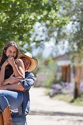 cowboy lifting up a girl outdoors