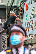 """Protestor Removal Unit of the police is seen removing the glued hand of a father and ex-teacher who climbed onto the canopy above the front door of the Department for Business and Energy building where he spray-painted '4 degrees = Mass murder' and unfurled a banner reading 'Act Now For All Our Children' on Monday, Sept 7, 2020. He said: """"My youngest child is only one. Within her lifetime scientists tell us that we are likely to see 4 degrees of global warming he continued. <br /> Environmental nonviolent activists group Extinction Rebellion enters its 7th day of continuous ten days protests to disrupt political institutions throughout peaceful actions swarming central London into a standoff, demanding that central government obeys and delivers Climate Emergency bill. (VXP Photo/ Vudi Xhymshiti)"""