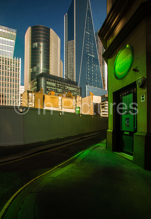 View of the City of London skyscrapers and building sites seen from Fenchurch Street, on 16th April 2020 in London, United Kingdom. Normally crowded with people London is like a ghost town as workers stay home under lockdown during the Coronavirus pandemic. The green glow comes from sunlight reflected from green tinted windows of one of the overlooking modern buildings.