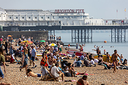 Licensed to London News Pictures. 06/09/2021. Brighton, UK. Sunbathers enjoy the hot sun on Brighton Beach, East Sussex as weather forecaster predict a mini-heatwave for September this week with temperatures hitting over 29c tomorrow. Photo credit: Alex Lentati/LNP
