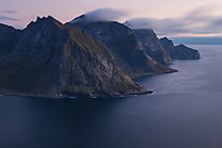 Steep mountain peaks rise from the sea on the wild northern coast of Moskenesøy, Lofoten Islands, Norway