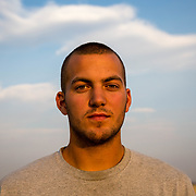 Gabe Stolfutz, 22, a college student from Lancaster County, PA, after cleaning a combine with an air compressor. This is his third season working on a wheat harvest. May through September harvest crews travel through America's heartland, following the wheat as it ripens. Near Hamer, Idaho, August 18, 2017.