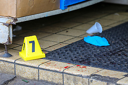 © Licensed to London News Pictures. 13/10/2019. London, UK. Evidence marker, medical glover and blood stains at the entrance of West Green Halal Meat and Groceries store on West Green Road in Tottenham, North London where two men were stabbed and rushed to hospital shortly after 9.30am this morning. The ages of the two victim and their condition is not yet know. Photo credit: Dinendra Haria/LNP