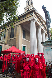 London, UK. 16 October, 2019. Extinction Rebellion's Red Rebel Brigade leave St John's church at Waterloo to take part in the day's International Rebellion Autumn Uprising protests outside Google and YouTube against the spread of systematic disinformation on climate change and in Trafalgar Square and Whitehall against the use by the Metropolitan Police of Section 14 so as to prohibit entirely Extinction Rebellion Autumn Uprising protests throughout the capital.