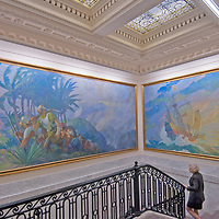 Paintings of classic exploration overhang the stairs leading to the formal boardroom at the National Geographic headquarters in Washington, DC.  Decending the stairs is Expeditions Council advisory board member Anne Giesecke.