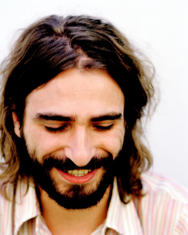 Portrait of a shy bearded man smiling looking down