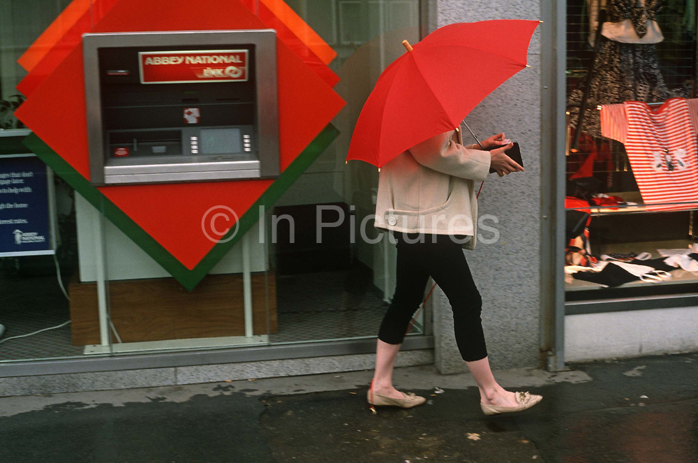 A lady walks away with an open wallet after taking cash from her local London branch of the Abbey National Building Society. While holding a red umbrella that hides her face, the woman walks away from the cash dispenser and we can see her purse or wallet, open for others to view. The red from her brolley and that of the dispenser's facia are matching hues so the dominant colour makes the picture's theme. Cash dispensers in the UK are also called 'holes in the wall' and dispense bank notes to high street consumers on demand. The downside is often compromised security when people are unaware of those watching alongside to see PIN numbers and how much money is being taken out.