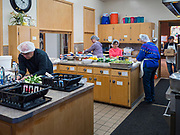 "26 FEBRUARY 2020 - FARMINGTON, MINNESOTA: Volunteers at the community dinner at Faith Church, work in the kitchen before the dinner. Faith Church is a United Methodist Church in Farmington, MN, about 30 minutes south of the Twin Cities. The dinner is sponsored by Loaves & Fishes, a Christian organization that provides food for community dinners and foodbanks. Farmington, with a population of 21,000, is a farming community that has become a Twin Cities suburb. The city lost its only grocery store, a Family Fresh Market, in December, 2019. The closing turned the town into a ""food desert."" In January, Faith Church started serving the weekly meals as a response to the store's closing. About 125 people per week attend the meal at the church, which is just a few blocks from the closed grocery store. The USDA defines food deserts as having at least 33% or 500 people of a census tract's population in an urban area living 1 mile from a large grocery store or supermarket. Grocery chains Hy-Vee and Aldi both own land in Farmington but they have not said when they plan to build or open stores in the town.     PHOTO BY JACK KURTZ"