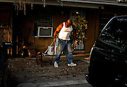 BRIAN CASSELLA       Times <br /> TP_303994_CASS_vidal_7 (03/04/2009 TAMPA) Vidal Mills walks with his dog, Red, in front of his West Tampa house. His son C.J. was killed in the yard by a drive-by shooter. VIDAL MILLS PROJECT -- Vidal Mills' son, C.J. Mills, 17, was a promising Jefferson High football star when he was shot and killed in front of his West Tampa home in 2007. No arrests have been made in his death. [BRIAN CASSELLA, Times]