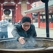 Man burning incense in the main courtyard at Senso-ji Temple in the Asakusa district of Tokyo.