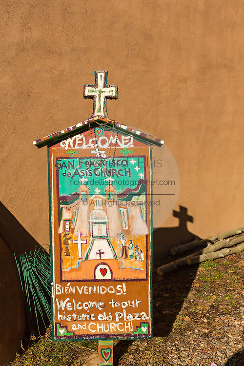 Folk art sign for the historic San Francisco de Asis Mission Church in Ranchos de Taos Plaza, Taos, New Mexico. The adobe church built in 1772 and made famous in paintings by artist Georgia O'Keeffe.