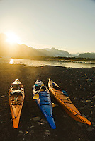 Three beached kayaks illuminated by the sunset at 10:30pm at Bear Lake , Kenai Fjords National Park, Alaska