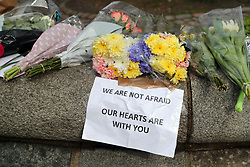 Flowers outside the Queen Elizabeth II Centre in London, after seven people were arrested in raids in London, Birmingham and elsewhere linked to the Westminster terror attack.