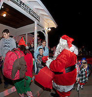 Santa Claus' arrival by fire truck delights family and friends gathered at the Wicwas Grange Saturday evening for their annual Christmas party.  (Karen Bobotas/for the Laconia Daily Sun)