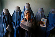 Amina, 13, center, who weaves carpets, is surrounded by her classmates who come in with burqas at the literacy center by an Afghan NGO, HAWCA (Humanitarian Assistance for the Women and Children of Afghanistan), Kabul, Afghanistan, Monday, Oct. 30, 2006. Five years after the Taliban's fall, Afghan women still suffer from illiteracy largely due to the opposition of the male members of the family such as fathers or husbands.